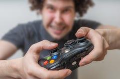 El hombre joven está jugando a los videojuegos y sostiene la palanca de mando o el regulador Fotos de archivo