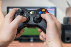 El hombre joven está jugando a los videojuegos y sostiene la palanca de mando o el regulador Fotos de archivo libres de regalías