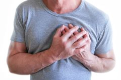 El hombre joven est? sufriendo de dolor de pecho Espasmo del pecho, angina de pecho Ataque del coraz?n fotografía de archivo