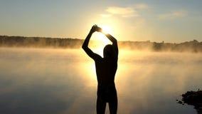 El hombre joven estira hacia fuera sus brazos en un banco del lago en la puesta del sol metrajes