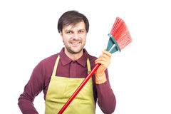 El hombre joven feliz con el delantal y los guantes que llevan a cabo un barrido, alistan a Fotografía de archivo libre de regalías