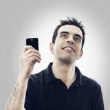 El hombre joven feliz con smartphone mira para arriba Imagen de archivo