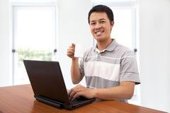 El hombre joven feliz disfruta de trabajo con el ordenador Foto de archivo libre de regalías