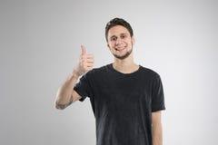 El hombre joven feliz en camisa negra aisló el estudio Foto de archivo