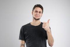 El hombre joven feliz en camisa negra aisló el estudio Imagenes de archivo