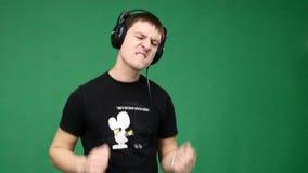El hombre joven feliz en los auriculares que bailan y escucha música en fondo verde almacen de video