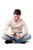 El hombre joven feliz escribe un mensaje Fotografía de archivo