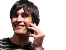 El hombre joven feliz está hablando por el teléfono fotos de archivo