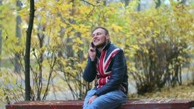 El hombre joven feliz hermoso está hablando por el teléfono móvil que se sienta en un banco cerca de arbustos amarillos almacen de video