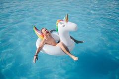 El hombre joven feliz se sienta en el flotador blanco y goza Él sonríe y mantiene ojos cerrados El individuo está en piscina sola fotos de archivo