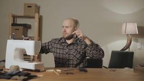 El hombre joven fija el carrete del hilo en la máquina Trabajo como sastre y usar una máquina de coser en un estudio de la materi metrajes