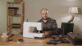 El hombre joven fija el carrete del hilo en la máquina Trabajo como sastre y usar una máquina de coser en un estudio de la materi almacen de metraje de vídeo
