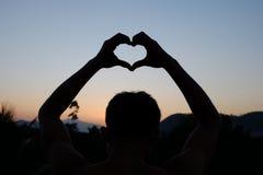 El hombre joven forma el corazón con puesta del sol Fotos de archivo