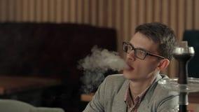 El hombre joven fuma la cachimba en café Imágenes de archivo libres de regalías