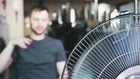 El hombre joven gira el ventilador en el trabajo Tema del calor del verano almacen de metraje de vídeo