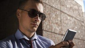 El hombre joven habla en el teléfono que se coloca en la calle almacen de video