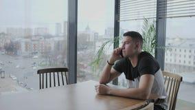 El hombre joven habla por el teléfono Trabajo del Freelancer sobre netbook en coworking moderno Programador en el trabajo remoto  almacen de metraje de vídeo