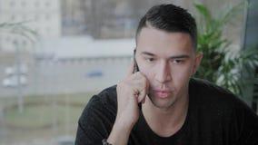 El hombre joven habla por el teléfono Trabajo del Freelancer sobre netbook en coworking moderno Programador en el trabajo remoto  metrajes