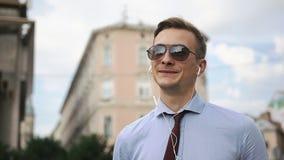 El hombre joven habla vía los auriculares en la calle metrajes