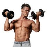 El hombre joven hace ejercicios con pesas de gimnasia Foto de archivo libre de regalías