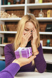 El hombre joven hace el regalo a una muchacha que la cierre los ojos Imagen de archivo libre de regalías