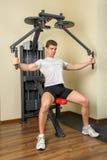 El hombre joven hace entrenamiento en la máquina de la mosca del pecho en gimnasio Imagen de archivo