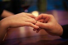 El hombre joven hace propuesta de matrimonio de la mujer y pone un compromiso r Fotos de archivo libres de regalías