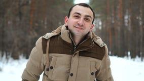 El hombre joven hace un marco de fingeres contra el contexto del bosque del invierno almacen de metraje de vídeo
