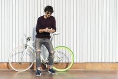 El hombre joven hermoso con el teléfono móvil y el engranaje fijo montan en bicicleta fotos de archivo libres de regalías