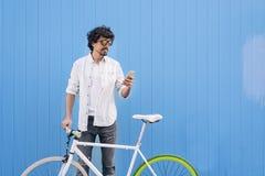 El hombre joven hermoso con el teléfono móvil y el engranaje fijo montan en bicicleta Foto de archivo libre de regalías