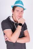 El hombre joven hermoso encantador en formalwear lleva a cabo un fondo azul del blanco del sombrero imagenes de archivo