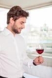 El hombre joven hermoso es relajante con la bebida del alcohol foto de archivo