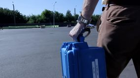 El hombre joven hermoso esposado a la pequeña caja protegida a prueba de balas azul sale de tiro ausente de la acción del paseo m metrajes
