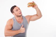 El hombre joven hermoso está comiendo la comida malsana Imagen de archivo