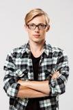 El hombre joven hermoso rubio confiado en los vidrios que llevaban la camisa de tela escocesa casual con las manos cruzó en el pe Imagen de archivo