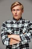 El hombre joven hermoso rubio sorprendido que llevaba la camisa de tela escocesa casual con las manos cruzó en el pecho que mirab Fotografía de archivo