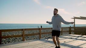 El hombre joven hermoso se está resolviendo, cuerda de salto en orilla de mar metrajes