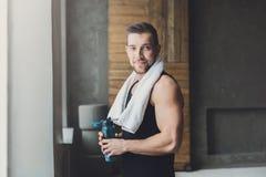 El hombre joven hermoso se relaja en el gimnasio después de entrenar foto de archivo