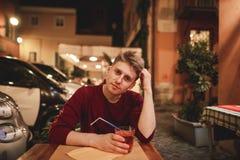 El hombre joven hermoso se sienta por la tarde en la terraza de un restaurante con un vidrio de alcohol foto de archivo