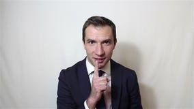 El hombre joven hermoso trae un finger a su boca que pide silencio almacen de video