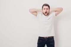 El hombre joven indignado con el pelo oscuro y la barba en camiseta grita a Imagenes de archivo