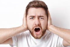 El hombre joven indignado con el pelo oscuro y la barba en camiseta grita a Imagen de archivo libre de regalías