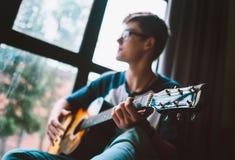 El hombre joven juega en la guitarra que se sienta cerca de la ventana Fotos de archivo