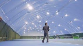 El hombre joven juega a tenis en el campo de tenis y su amigo observa después de su juego almacen de metraje de vídeo