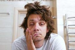 El hombre joven lanudo soñoliento mira el espejo en cuarto de baño por la mañana fotos de archivo