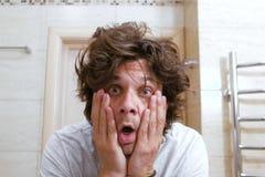 El hombre joven lanudo soñoliento mira el espejo en el cuarto de baño por la mañana y sorprendido fotos de archivo