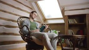 El hombre joven lee un libro en el ático metrajes