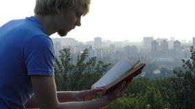 El hombre joven lee un libro en un encintado de una plataforma de observación metrajes