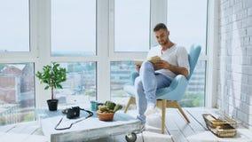 El hombre joven leyó el libro que se sentaba en balcón en el apartamento moderno imagen de archivo