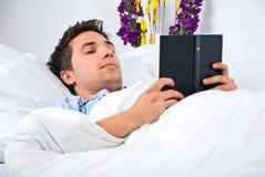 El hombre joven leyó un libro en su cama Foto de archivo